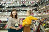带孩子的女人选择婴儿鞋 — 图库照片