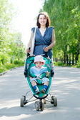 Woman with stroller at summer park — Stock Photo
