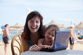 ビーチでのノート パソコンとの幸せな家族 — ストック写真