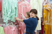 Happy mother and daughter at clothes shop — Stock Photo