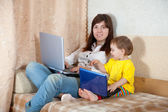 Frau mit kleinkind, die mit laptops im wohnzimmer — Stockfoto