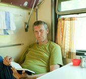 Man reading book in sleeper train — Stock Photo