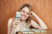Happy girl with US dollars in home — Stock Photo