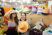 Women chooses hat at shop — Stock Photo