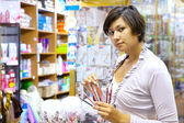 Woman chooses the cosmetic pencil — Stock Photo