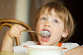 Child himself eats cereal — Stock Photo