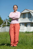 Happy woman against her home — Stock Photo