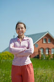 Happy mature woman against her home — Stockfoto