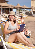 Happy woman sitting with laptop at beach — Stock Photo