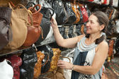 Mature woman chooses leather bag — Stock Photo