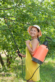 Woman spraying tree branches — Stock Photo