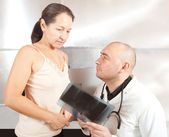 Doctor with patient looking x-ray — Stock Photo