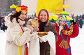 Girl tasting pancake during Shrovetide — Foto de Stock