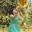 Girl throwing maple leaves in the air — Stock Photo #12495533
