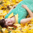Young woman lies in autumn park — Stock Photo #12495548