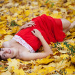 Young woman lies in maple leaves — Stock Photo #12495551