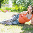 Pregnant woman on grass - Stockfoto