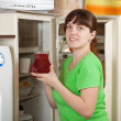 Woman putting jug with fruit-drink into fridge - Stok fotoğraf