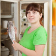 Woman putting  frozen fish into refrigerato - Stockfoto