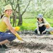 Women and kid sows seeds - Stock Photo