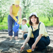 Women with child works at garden - Foto Stock