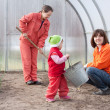 Happy family works in greenhouse - Stock Photo