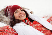 Happy girl lying down on snow — Stock Photo