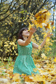 Meisje gooien esdoorn bladeren in de lucht — Stockfoto