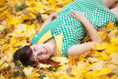 Young woman lies in autumn park — Stock Photo