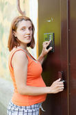 Pregnant woman using house intercom — Stock Photo