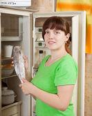 Woman putting frozen fish into refrigerato — Stock Photo
