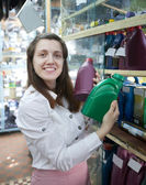 Woman chooses motor oil in auto parts store — Stock Photo