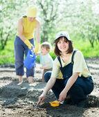 Donne con bambino opere al garden — Foto Stock