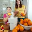 Women making fresh orange juice — Stock Photo