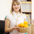 Businesswoman with basket of orange — Stock Photo #12502936
