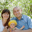 Happy family against spring bloom — Stock Photo #12508757