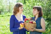 Girls with apples in garden — Stock Photo
