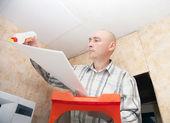 Guy glues ceiling tile — Stock Photo