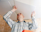 Man glues ceiling tile — Stock Photo