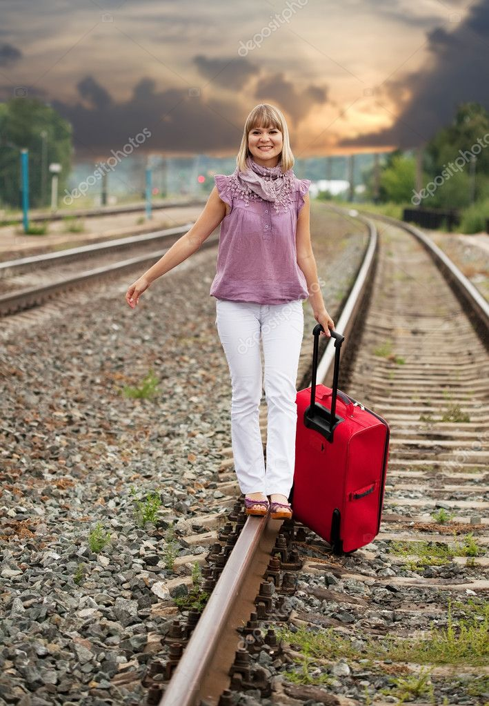 Happy woman with luggage walking on rail — Stock Photo #12503020