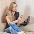 Girl speaks by mobile and uses laptop — Stock Photo #12510055