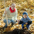 Woman with   son setting tree in autumn - Stock Photo