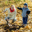 Woman with  son resetting  tree in autumn — Stock Photo