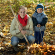 Woman with  son working  in autumn - Stock Photo