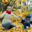 Mother with boy throw up maple leaves — Stock Photo #12510812