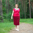 Woman walking in pine forest — Stock Photo