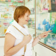Stock Photo: Woman chooses enema at pharmacy