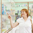 Stock Photo: Womchooses drugs at pharmacy