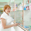 Woman chooses at the pharmacy — Stock Photo