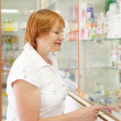 Woman near counter in pharmacy — Stock Photo